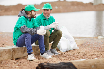 Two volunteers in green uniform sitting with paper cups and resting on polluted shore
