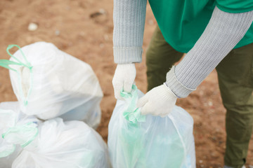 Crop unrecognizable volunteer with bag full of litter on shore