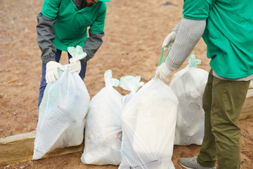Crop unrecognizable volunteers standing on sand and tying bags with litter