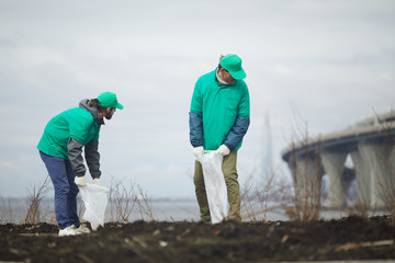 Two volunteers men standing on shore in cloudy day and collecting garbage