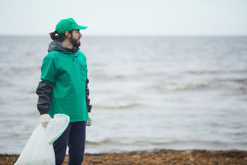 Young volunteer man in green uniform with bag standing on coast and looking away