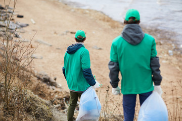 Back view of unrecognizable activists in green uniform walking to polluted shore with garbage bags