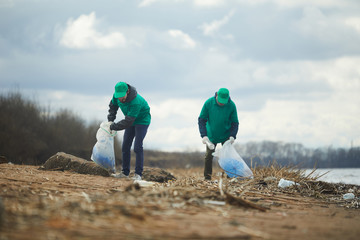 Two volunteers men in green uniform standing and collecting garbage on shore