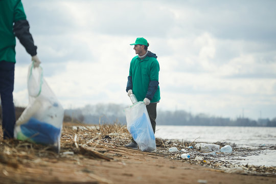 Two activists men working and collecting garbage to bags on polluted shore
