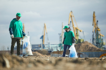 Two volunteers men in green uniform working and collecting rubbish on construction site