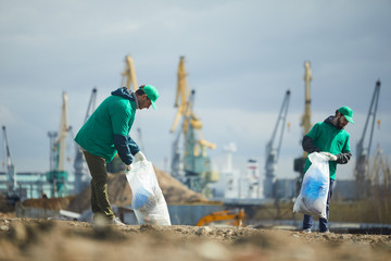 Two volunteers in green uniform picking garbage on construction site