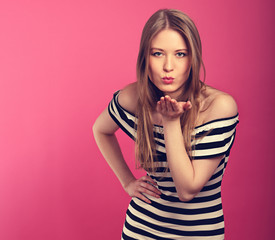 Beautiful sexy woman showing a kissing sign and blowing the lips on the hand in fashion stripped dress on pink background. Closeup portrait