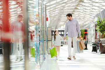 Charming little girl holding hand of father and walking together in shopping center carrying colorful papers bags