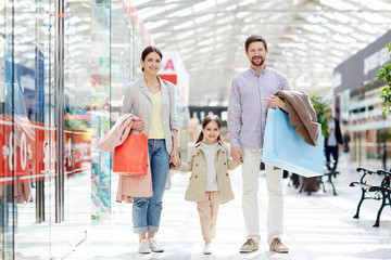 Adult cheerful parents with little girl carrying paper bags and standing in mall smiling at camera enjoying shopping together