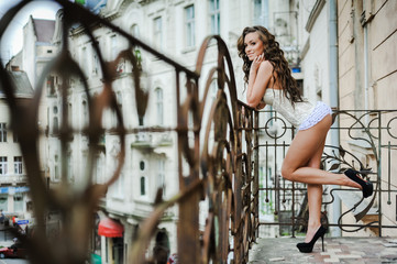 Beautiful young woman posing in underwear on the balcony of the old city