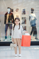 Cute little girl with red paper bag and plush toy smiling and looking at camera while standing near display window in modern mall