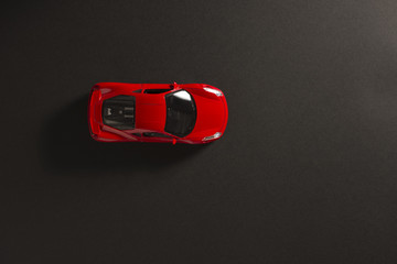 Red toy sports car on a black background.