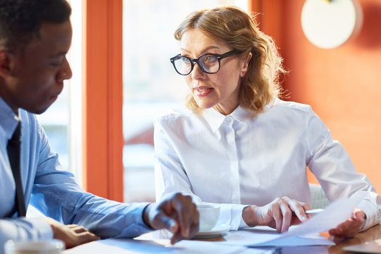 Adult serious woman in shirt and glasses having document and talking to black man having serious meeting