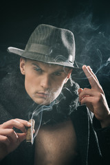 Vintage detective concept. Man in coat, hat smoking cigar, dark background. Guy in old fashioned outfit looks mysterious with cigar and smoke. Macho on mysterious face, detective, investigator, agent.