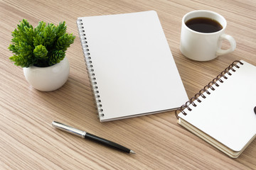 Notebook with coffee cup and potted plant on wood desk. Text copy space.