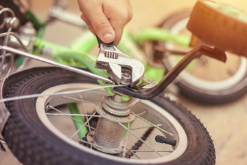 Father repairing his kids bicycle. Removing Bike's Training Wheels.