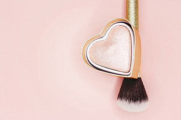 Golden brush for make-up on a pink background with glitter