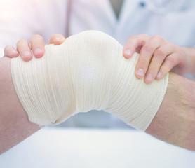 traumatologist ,applying a bandage on the knee