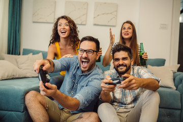 Portrait of group of friends playing video games at home