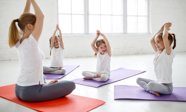 children practicing engaged in gymnastics and yoga with  teacher.