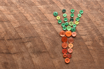 a carrot made with sewing buttons on wood