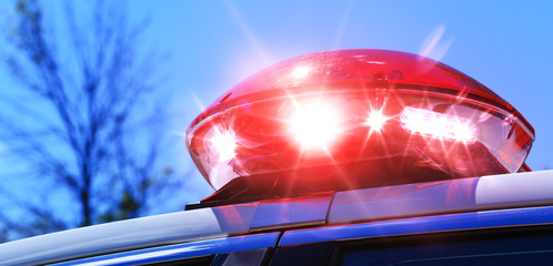 Police car with focus on red siren light. Colorful red siren on the roof of a police car in a real intervention. Beautiful red siren lights activated in full policemen operation. Red light siren.