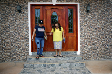 Sisters Emily and Isilda Hernandez leave Emily's house in Intipuca, El Salvador