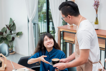 Asian male barista holding coffee cup served to customer at table,Cafe restaurant service concept,Owner small business concept.