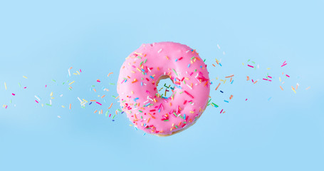 one pink flying sweet doughnut with sprincles on blue banner