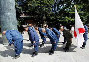 Right wing group members bow their heads to pay tribute to the war dead at Yasukuni Shrine in Tokyo