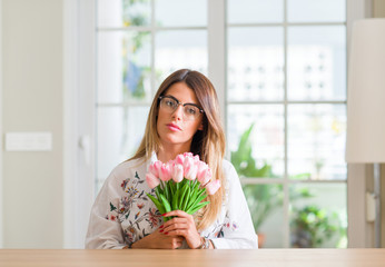 Young woman at home holding pink tulips flowers with a confident expression on smart face thinking serious