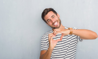Handsome young man over grey grunge wall wearing navy t-shirt smiling in love showing heart symbol and shape with hands. Romantic concept.