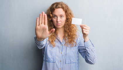 Young redhead woman over grey grunge wall holding blank visit card with open hand doing stop sign with serious and confident expression, defense gesture