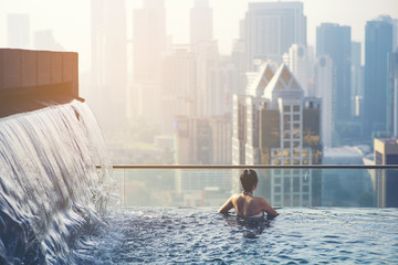 Asian travel. young woman enjoying the city view from roof top swimming pool. Wall mural