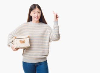 Young Chinese woman over isolated background holding a box surprised with an idea or question pointing finger with happy face, number one