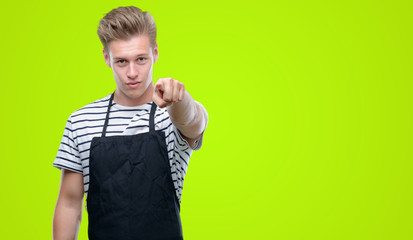 Young handsome blond man wearing apron pointing with finger to the camera and to you, hand sign, positive and confident gesture from the front