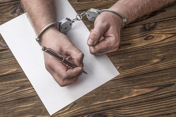 Men's hands with handcuffs fill the police record, confession. on top see the police investigative detective. Arrest, bail, criminal, prison.