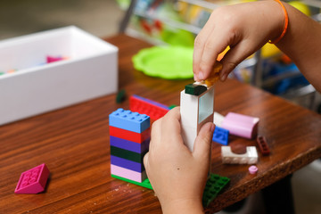 Kid playing with blocks from toy