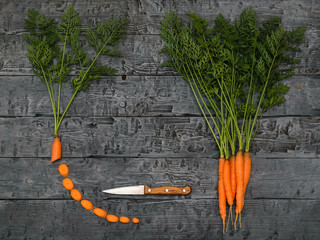 Sliced carrots, knife and a bunch of carrots on a dark rustic table. The view from the top. Flat lay.