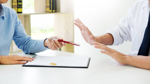 Closeup of a man do not want to Signing Contract or premarital agreement, filling petition form agreement of divorce in office at lawyer desk in court room  Conceptual of marriage