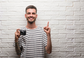 Young man holding vintage camera standing over white brick wall surprised with an idea or question pointing finger with happy face, number one