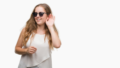 Young blonde woman wearing sunglasses smiling with hand over ear listening an hearing to rumor or gossip. Deafness concept.