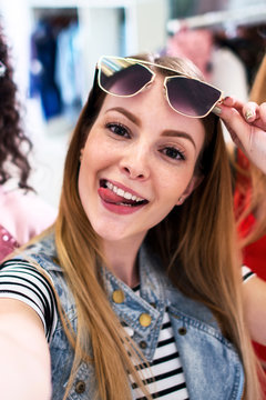 Smiling girlfriends wearing stylish sunglasses having fun time taking selfie with mobile phone while doing shopping in clothing store