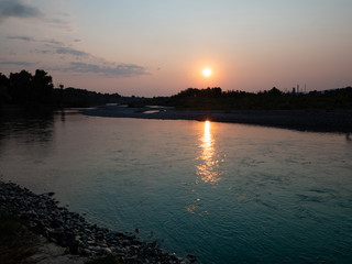Sunrise Over a River with a Rocky Bank. The sun is reflected in the water.