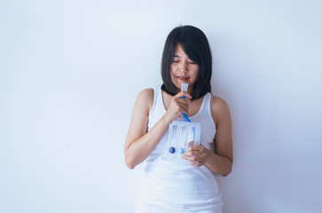 Patient asian woman using incentive spirometer or three balls for stimulate lung on white blackground