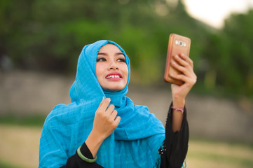 lifestyle portrait of young happy and beautiful tourist woman in muslim hijab head scarf taking selfie picture with mobile phone posing alone in holidays travel