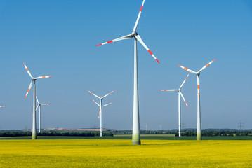 Modern wind wheels in a field of blooming rapeseed oil seen in Germany