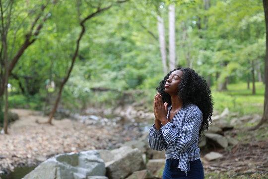 Pure black woman praying in nature