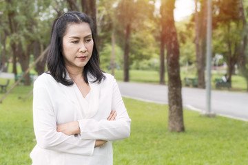 Beautiful portrait of senior woman thinking and relaxing at the park.Copy space.