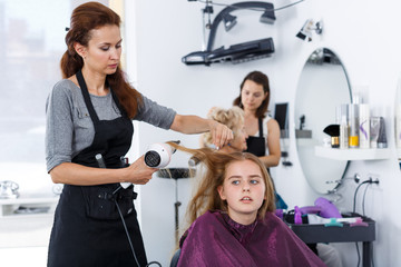 Stylist drying hair for teenage girl
